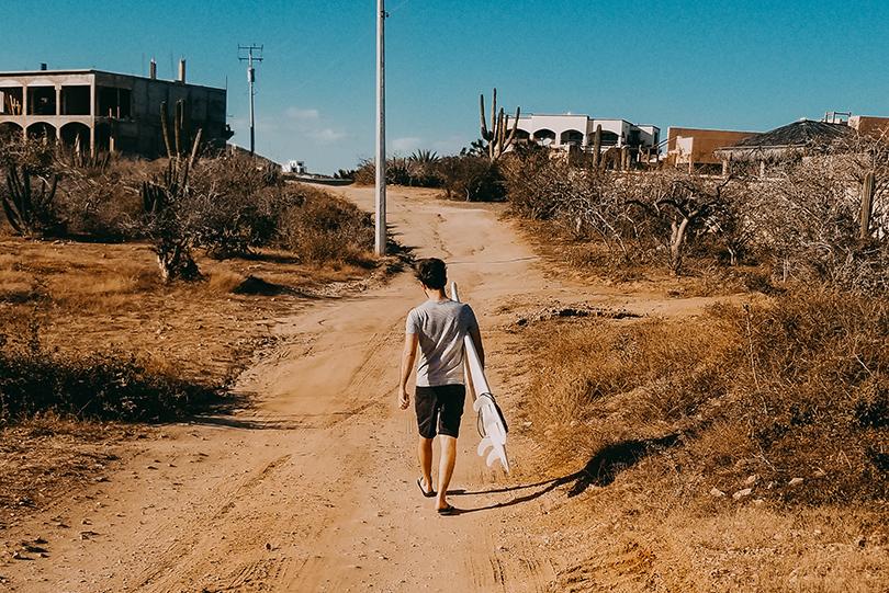 La planche de surf sous le bras à El Pescadero, par Côté Hublot